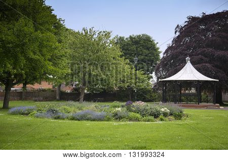 A bandstand and a colourful flowerbed in a park