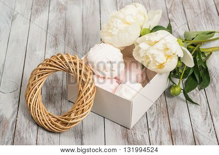 A box of marshmallows next to white peonies flowers on a white wooden background.