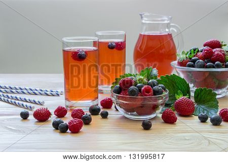 Two glasses of compote of raspberries strawberries blueberries near bowl with berries right carafe compote on a light wooden background scattered berries. Fresh berries compote. Horizontal.