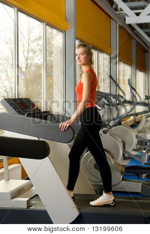 Beautiful young woman running on a treadmill in a gym alone
