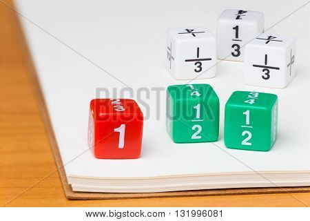 Colored fraction dices on blank white paper notebook on wooden desk selective focus on dices