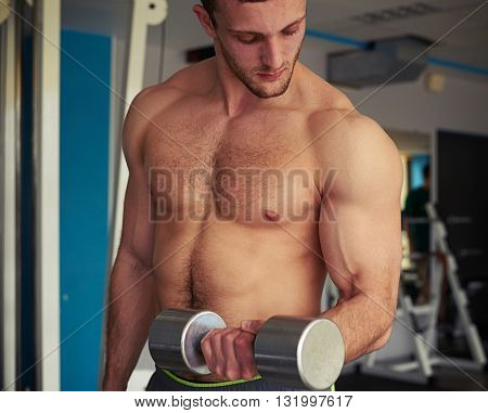 Young strong man with bare chest is lifting a dumbbell