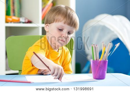 Cute little boy is drawing with color pencils in nursery room