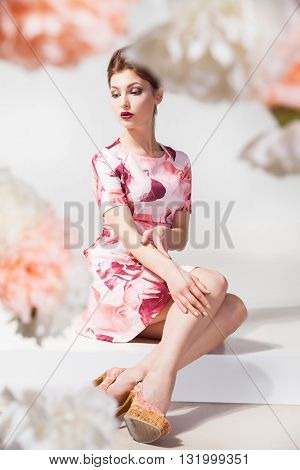 Portrait of beautiful young woman in dress sitting on floor.Flowered shot frame