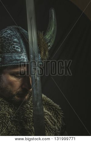 Viking warrior with iron sword and helmet with horns