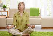 Постер, плакат: Женщина сидящая на этаже дома делает йога медитации