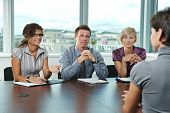 Panel of business people sitting at table in meeting room conducting job interview talking with appl
