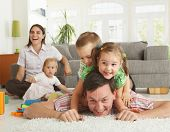 image of happy family  - Happy family having fun on floor of in living room at home - JPG