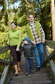 stock photo of nuclear family  - Happy family walking on bridge in autumn forest together - JPG