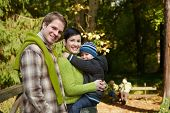 foto of nuclear family  - Portrait of happy family of three smiling at camera on autumn hiking - JPG