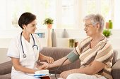 Female doctor measuring blood pressure of senior woman at home.?