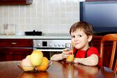 stock photo of orange-juice  - Little boy is drinking a juice at home - JPG