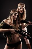 stock photo of girls guns  - Two sexy women in military uniform posing against black background - JPG