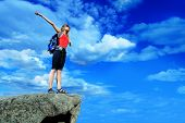 Woman tourist is standing at the top of a mountain with a feeling of freedom. poster