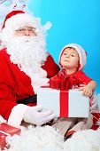Christmas theme: Santa Claus and little boy with presents.