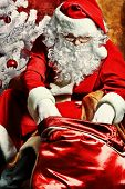 foto of santa-claus  - Santa Claus with presents and New Year tree at home - JPG