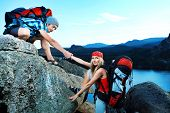 Couple of tourists are standing at the top of a mountain with a feeling of freedom. poster