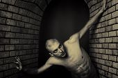 pic of skinhead  - Portrait of a muscular man posing in a closed space over black background and brick wall - JPG