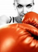 stock photo of revenge  - Sepia portrait of a girl in red boxing gloves - JPG