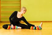 picture of leg warmer  - Ballet dancer doing stretching exercise on a floor - JPG