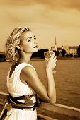 Beautiful blond girl drinks champagne near the rive