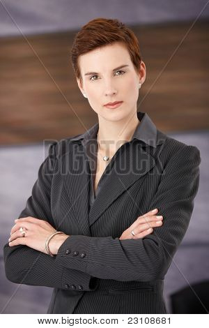 Trendy determined businesswoman standing in office with arms folded, looking at camera.?