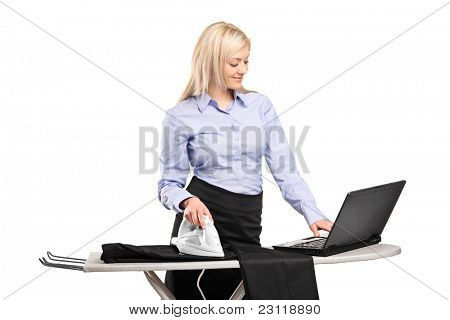 Blond businesswoman ironing his clothes and working on a laptop isolated on white background
