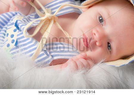 Closeup Of Baby Boy Lying On Side In Furry Basket