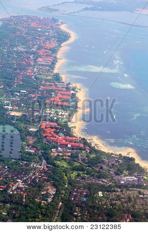 Sandy coast, buildings and blue sea with waves. Bali island view from plane