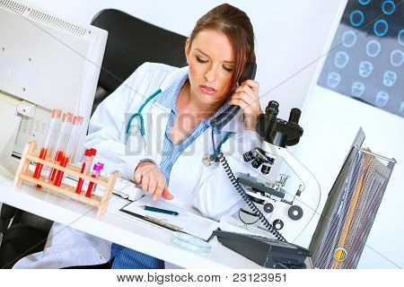 Concerned Doctor Woman Talking On Phone And Looking In Clipboard