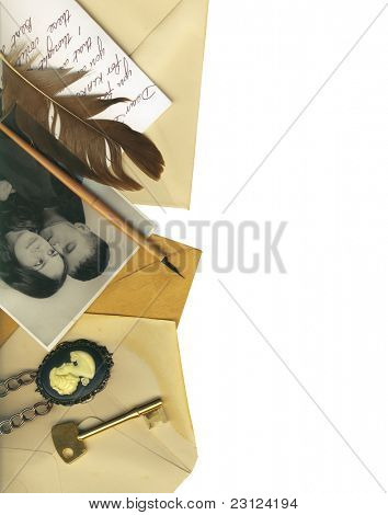 Clipping path. Vintage border with old letters, a key, a vintage photo, a cameo and an old feather.