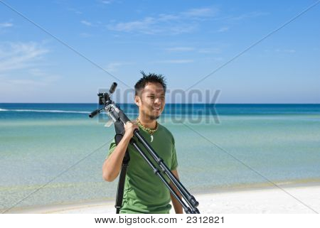 Photographer Carrying Tripod On The Beach