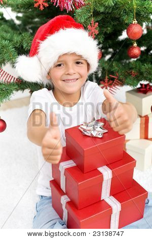 Happy boy with christmas hat and presents giving thumbs up sign