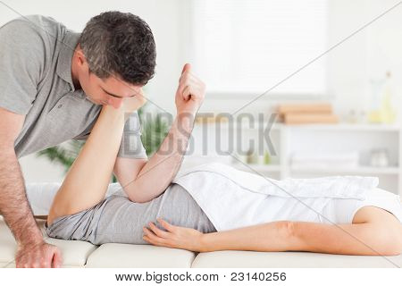 Chiropractor Stretches Customer's Leg