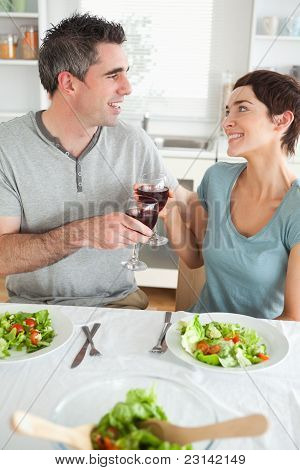 Close Up Of A Happy Couple Toasting With Redwine