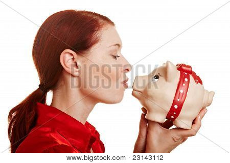 Redhaired Woman Kissing A Piggy Bank