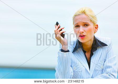 Mujer de negocios indignado con teléfono celular, apoyado en la barandilla en edificio de oficinas