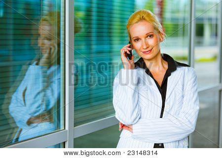 Smiling Business Woman Talking On Mobile At Office Building
