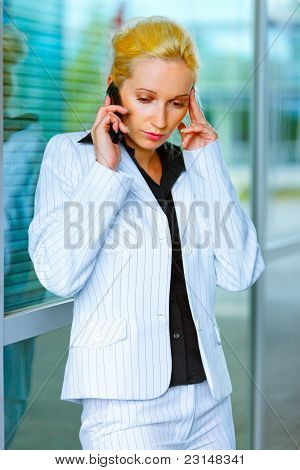 Strained Business Woman Talking On Mobile At Office Building
