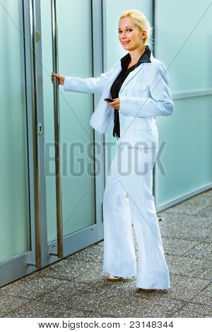 Full Length Portrait Of Smiling Business Woman Entering Office Building