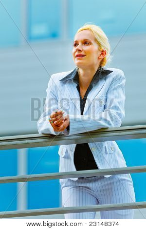 Pensive Business Woman Leaning On Railing At Office Building Looking In Corner