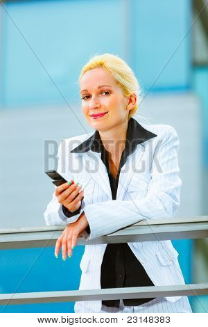 Business Woman With Cell Phone Leaning On Railing At Office Building