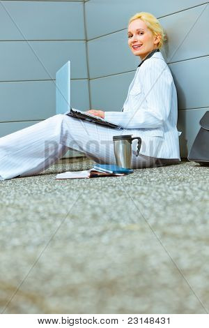 Smiling Business Woman On Floor At Office Building Working On Laptop