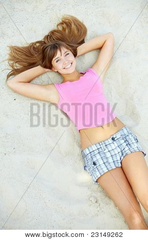 Above angle of pretty teenager lying on sand and laughing
