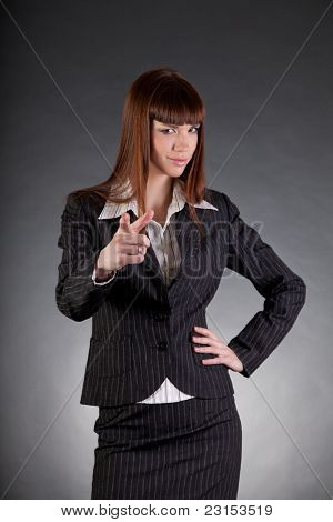Serious looking business woman pointing in camera, studio shot