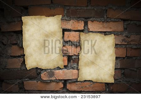 Old blank papers on a brick wall