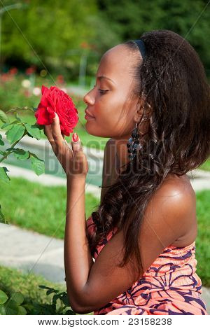 Portrait Of A Young Beautiful African American Girl  Smelling Fl