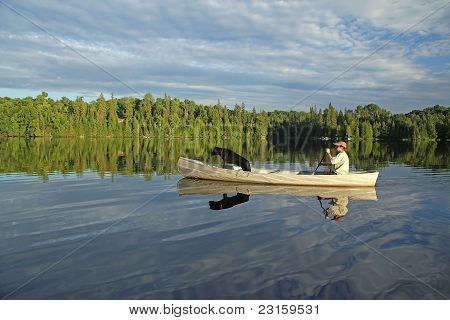 Canoeist and LPaddling a Canoe on a Northern Ontario Lake with a Black Labrador Retriever in the Bow