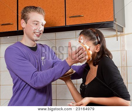 Young man putting a cream pie in his girlfriend's face