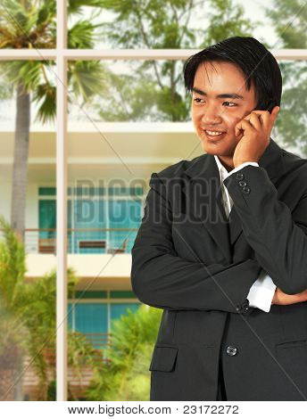 Asian Business Man Talking On The Phone In His Home